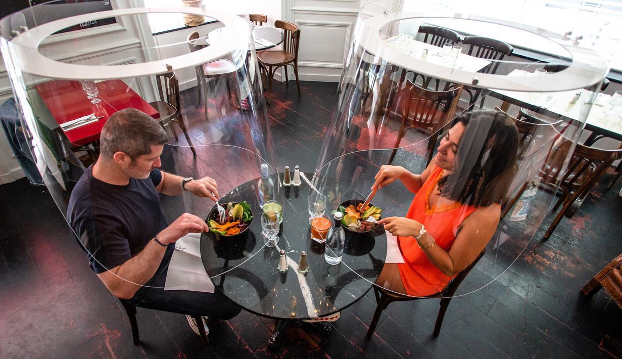 Sejumlah orang berpose di bawah purwarupa gelembung plexiglass Plex'Eat di restoran H.A.N.D di Paris, Prancis, pada 27 Mei 2020. Pelindung plexiglass Plex'Eat untuk menyelubungi pengunjung sehingga melindungi mereka dari virus corona Covid-19. (Xinhua/Aurelien Morissard)