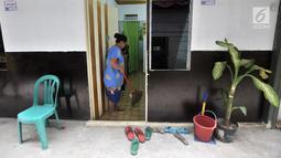 Warga menyapu kediamannya yang berada di penampungan sementara (shelter) Kampung Kunir, Tamansari, Jakarta, Selasa (18/9). Masing-masing rumah di Shelter Kampung Kunir memiliki luas 18 meter persegi. (Merdeka.com/Iqbal Nugroho)