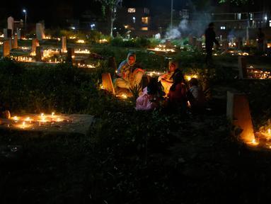 Sejumlah warga Kashmir menyalakan lilin di pemakaman keluarga dan saudara mereka saat memperingati Shab-e-Barat di pinggiran Srinagar, Kashmir (1/5). Selain itu mereka juga berdoa untuk sanak keluarga mereka. (AP Photo / Mukhtar Khan)