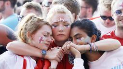 Tiga orang fans saling berpelukan usai timnas Inggris gagal melaju ke final Piala Dunia di Hyde Park, London, Rabu (11/7/2018). Kroasia menang 2-1 atas Inggris. (AP/Matt Dunham)