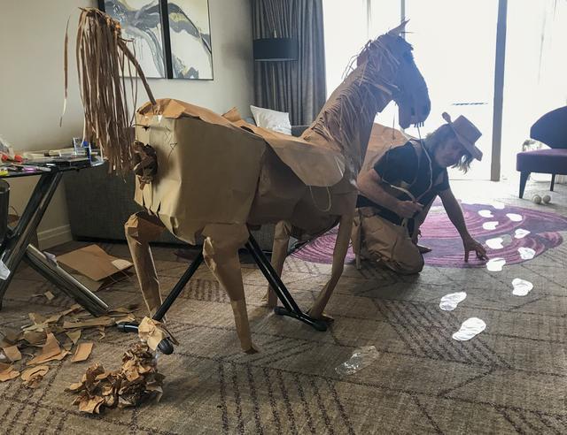 David Marriott berpose dengan kuda kertasnya Russell di kamar hotelnya di Brisbane, Australia, 3 April 2021. Saat berada dalam kamar hotel untuk karantina, direktur seni di iklan TV itu bosan dan mulai membuat pakaian koboi dari kantong kertas makanannya yang dikirimkan. (David Marriott via AP)