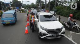 Petugas gabungan menghentikan pengendara mobil yang hendak menuju Puncak di Simpang Gadog, Bogor, Kamis (24/12/2020). Polisi bakal menutup jalur Puncak guna mengantisipasi lonjakan volume kendaraan dan penyebaran Covid-19 seiring peringatan malam tahun baru. (merdeka.com/Arie Basuki)