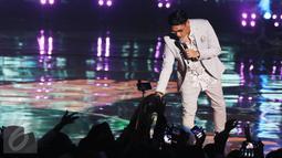 Penyanyi Afgansyah Reza menyapa penonton di atas panggung HUT 26 SCTV di Istora Senayan, Jakarta, Rabu (24/8). Malam itu, Afgan membawakan lagunya yang berjudul 'Kunci Hati'. (Liputan6.com/Herman Zakharia)