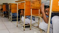 Sejumlah siswa berlindung di bawah meja saat simulasi bencana gempa dan tsunami di sebuah sekolah di Banda Aceh, Aceh, Rabu (9/10/2019). Simulasi dilakukan karena Aceh merupakan daerah rawan kedua bencana tersebut dan turut merusak bangunan sekolah. (Photo by CHAIDEER MAHYUDDIN / AFP)