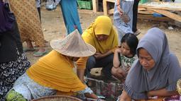 Pedagang ikan melayani pembeli di kawasan Pasar Sumur Jaya, Pandeglang, Banten, Sabtu (3/8/2019). Hingga saat ini tidak ada kerusakan yang berarti di kawasan Kecamatan Sumur usai gempa bermagnitudo 6,9 mengguncang Banten. (merdeka.com/Arie Basuki)