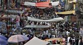 Orang-orang mengabaikan jarak sosial dan banyak yang tidak memakai masker wajah saat berbelanja untuk liburan Idul Fitri mendatang yang menandai akhir bulan suci puasa Ramadhan setelah pemerintah mengumumkan pembatasan baru, di Rawalpindi, Pakistan, Rabu (5/5/2021). (AP Photo/Anjum Naveed)