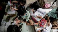 Sejumlah murid SD mengikuti kegiatan pembelajaran jarak jauh di sebuah pos keamanan RT 003 RW 006 Bendungan Hilir, Tanah Abang, Jakarta, Jumat (14/8/2020). Selain itu, mereka juga mengerjakan tugas sekolah yang diberikan oleh guru melalui aplikasi pesan singkat. (Liputan6.com/Faizal Fanani)