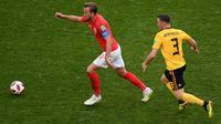 Penyerang Inggris, Harry Kane menggiring bola dari kawalan bek Belgia, Thomas Vermaelen saat bertanding memperebutkan juara tiga Piala Dunia 2018 di Stadion St. Petersburg, Rusia, (14/7). Belgia menang 2-0 atas Inggris. (AFP Photo/Olga Maltseva)