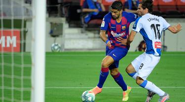 Penyerang Barcelona, Luis Suarez berebut bola dengan bek Espanyol, Leandro Cabrera pada lanjutan pertandingan La Liga Spanyol di Camp Nou, Kamis (9/7/2020) dini hari WIB.  Barcelona menang tipis 1-0 atas Espanyol lewat gol yang dicetak Luis Suarez. (LLUIS GENE / AFP)