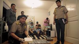 Petugas menunjukkan kokain berbentuk batu bata yang berhasil diamankan di sebuah apartemen di Miraflores, Lima, Peru, Selasa (22/3). 52 batu bata kokain diamankan dari tangan tiga tersangka, dua di antaranya berasal dari Prancis. (REUTERS/Guadalupe Pardo)