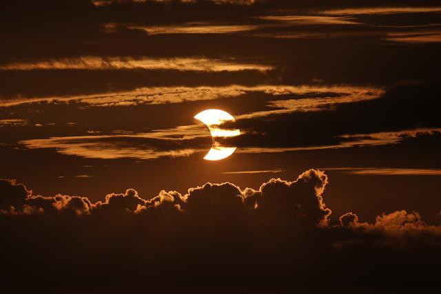 Gerhana matahari sebagian muncul di balik awan, Arbutus, Md, Kamis (10/6/2021).  (AP Photo/Julio Cortez)