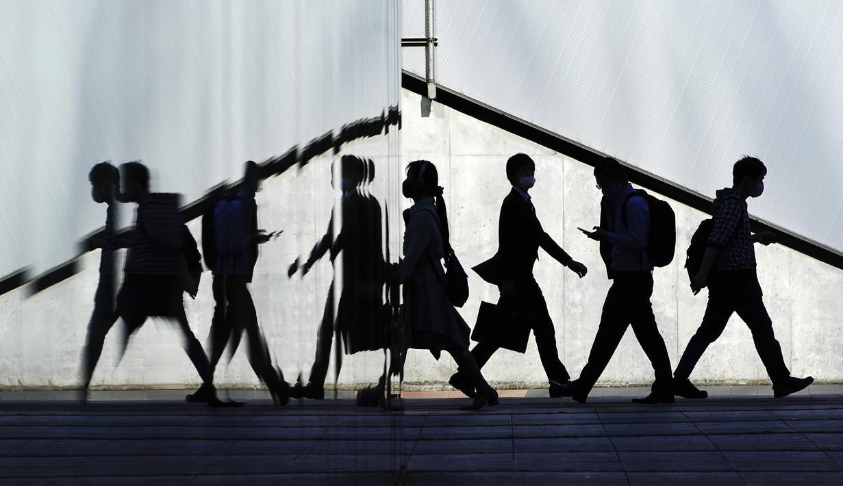 Orang-orang yang memakai masker pelindung untuk membantu mengekang penyebaran virus corona di Tokyo (21/4/2021). Ibukota Jepang mengonfirmasi lebih dari 840 kasus virus corona baru pada hari Rabu. (AP Photo/Eugene Hoshiko)