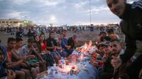 Warga bersiap buka puasa di pantai Rabat, Maroko (9/6). Selama Ramadan, banyak warga Maroko berkunjung ke pantai menikmati angin Atlantik dan menikmati pemandangan laut. (AP Photo/Mosa'ab Elshamy)