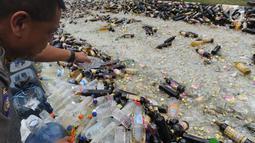 Petugas membuang minuman keras (miras) hasil sitaan saat pemusnahan di halaman Polres Bogor, Cibinong, Kamis (17/5). Miras yang dimusnahkan lebih dari 32 ribu botol, baik lokal maupun impor dengan beragam merek. (Merdeka.com/Arie Basuki)
