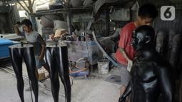 Para pekerja menyelesaikan pembuatan maneken di Kebon Jeruk, Jakarta Barat, Senin (28/12/2020). Pandemi COVID-19 berdampak pada sepinya pesanan pembuatan patung yang biasa dipakai untuk memajang pakaian tersebut. (merdeka.com/Dwi Narwoko)