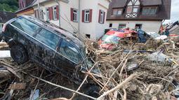 Sebuah mobil tertutup puing-puing menyusul bencana banjir dahsyat di Kota Braunsbach, Senin (30/5). Banjir melanda wilayah barat Jerman setelah hujan deras terjadi sepanjang Ahad (29/5) yang menewaskan empat orang. (Marijan Murat/dpa/AFP)