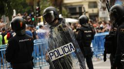 Polisi berjaga di lokasi aksi sopir taksi Spanyol, Madrid, Selasa (30/5). Demonstran menganggap layanan mobil berbasis online yang murah bisa menyebabkan layanan taksi ditinggalkan penumpang. (AP Photo / Francisco Seco)