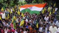 Pengunjuk rasa dari Front Rakyat Pribumi Tripura (IPFT) mengibarkan bendera India saat menggelar demo di Khamtingbari di dekat perbatasan Agartala, India, Senin (10/7). Mereka menuntut negara bagian Tripura terpisah. (AFP Photo/ Arindam Dey)