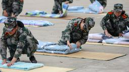 Mahasiswa baru belajar melipat selimut selama sesi pelatihan militer di sebuah kampus di Yangzhou, Jiangsu, China, Jumat (6/9/2019). Pelatihan militer bagi mahasiswa baru di China  biasanya dilakukan pada akhir liburan musim panas. (STR/AFP)