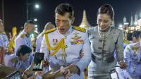 Raja Maha Vajiralongkorn dan Ratu Suthida menyapa pendukungnya di Bangkok, Thailand, Minggu, 1 November 2020. (Foto AP / Wason Wanichakorn)