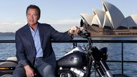 Mantan Gubernur California, Arnold Schwarzenegger berpose dengan duduk di atas motor Harley Davidson saat mempromosikan film terbarunya, `Terminator Genisys` di depan Sydney Opera House, Australia, Kamis (4/6/2015). (REUTERS/David Gray)