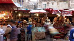 Para pedagang kurma melayani pembeli selama bulan suci Ramadan di sebuah pasar di ibukota Sanaa, Yaman (22/5). (AFP Photo/Mohammed Huwais)