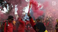 Sejumlah buruh menyalakan bom asap saat menutup aksi Hari Buruh Internasional di Jalan Medan Merdeka Barat, Jakarta, Rabu (5/1/2019). Buruh dari berbagai organisasi merayakan Hari Buruh Internasional di Kawasan Silang Barat Daya Monas. (Liputan6.com/Helmi Fithriansyah)