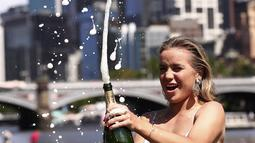 Petenis asal AS Sofia Kenin menyemprotkan sampanye pada sesi pemotretan di Sungai Yarra setelah kemenangannya atas Garbine Muguruza dari Spanyol di final tunggal putri kejuaraan tenis Australia Terbuka di Melbourne, Australia, Minggu, (2/2/2020). (AP Photo/Dita Alangkara)
