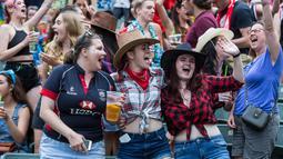 Sejumlah wanita bersorak saat menyaksikan hari pertama turnamen rugby sevens Hong Kong, China (6/4). Turnamen ini berlangsung selama tiga hari dan diselenggarakan setiap tahun oleh Hong Kong Rugby Union (HKRU). (AFP Photo/Isaac Lawrence)