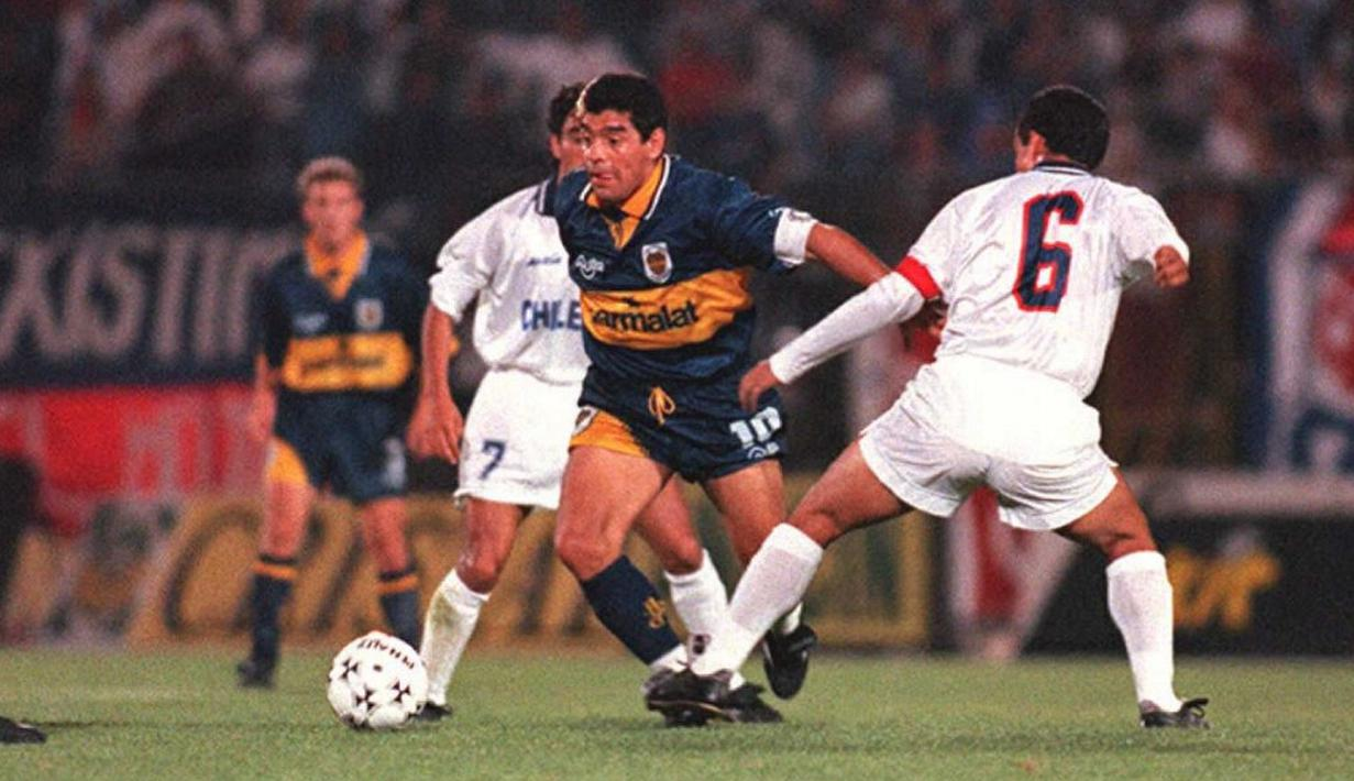 Pemain sepak bola Boca Juniors Diego Maradona (tengah) mencoba menghindari pemain Universidad de Chile Ronald Fuentes pada pertandingan persahabatan di Santiago, Chile, 12 Desember 1995. Legenda sepak bola Argentina Diego Maradona meninggal dunia pada 25 November 2020. (MARTIN THOMAS/AFP)