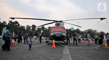 Helikopter TNI terparkir di kawasan Monas, Jakarta, Rabu (16/10/2019). Kehadiran empat helikopter TNI/Polri yang akan digunakan dalam apel pengamanan pelantikan presiden dan wakil presiden tersebut menarik perhatian pengunjung Monas. (merdeka.com/Iqbal Nugroho)