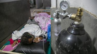 Seorang pasien COVID-19 menerima oksigen di koridor bangsal gawat darurat rumah sakit di Kathmandu, Rabu (5/5/2021). Lockdown di ibu kota Kathmandu dan distrik sekitarnya diperpanjang ketika negara Himalaya mencatat infeksi harian COVID-19 dan kematian tertinggi. (AP Photo/Niranjan Shrestha)