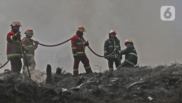 Petugas Pemadam Kebakaran Kabupaten Bogor memadamkan api di lapak ban bekas, Desa Bojong Nangka, Gunung Putri, Kamis (22/4/2021). Banyaknya bahan yang mudah terbakar dan sumber api yang berasal dari bawah tumpukan ban membuat  api di lokasi belum juga padam. (Liputan6.com/Herman Zakharia)