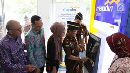Kejati DKI Jakarta Tony T Spontana (kanan) melakukan transaksi pembayaran tilang online disaksikan SVP Hubungan Kelembagaan Bank Mandiri Dadang Ramadhan (kiri) di kantor Kejaksaan Negeri Jakarta Pusat, Jakarta, Kamis (3/1). (Liputan6.com/Angga Yuniar)