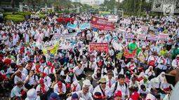 Massa membawa berbagai atribut dalam aksi damai di depan Istana Negara, Jakarta, Rabu (19/7). Mereka mendesak agar para pegawai non PNS yang telah mengabdi pada garda depan pelayanan publik, bisa diangkat menjadi PNS. (Liputan6.com/Faizal Fanani)
