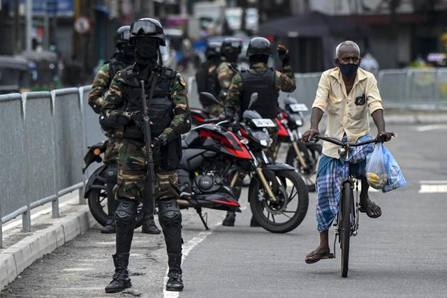 Tentara Sri Lanka berjaga-jaga di pos pemeriksaan saat negara itu bersiap untuk lockdown di Kolombo, Selasa (25/5/2021). Sri Lanka bersiap menerapkan lockdown ketat selama dua minggu untuk menekan penyebaran corona Covid-19. (ISHARA S. KODIKARA / AFP)