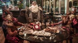 Suasana Natal terlihat di dalam restoran yang tutup di pusat kota Athena, Yunani pada 21 Desember 2020. Yunani akan merayakan musim Natal di bawah langkah-langkah penguncian wilayah atau lockdown akibat virus corona COVID-19 hingga 7 Januari 2021 mendatang. (LOUISA GOULIAMAKI/AFP)