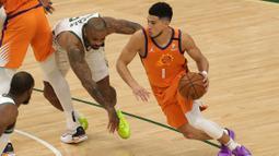 Walaupun tampil di hadapan pendukungnya, Bucks harus kesulitan membendung serangan Suns di awal pertandingan. Devin Booker (kanan) berhasil tampil gemilang dan bawa Suns unggul 23-20 di kuarter pertama. (Foto: Getty Images via AFP/Stacy Revere)