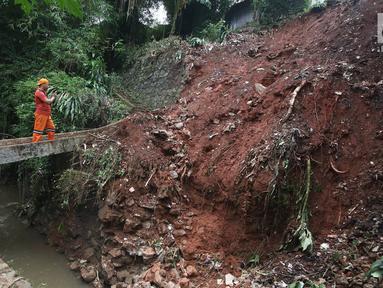 Warga berdiri didekat longsoran yang terjadi di kawasan Ciganjur, Jakarta Selatan, Senin (13/11).  Longsor diduga akibat penumpukan material pembangunan serta hujan deras yang mengguyur Jakarta. (Liputan6.com/Immanuel Antonius)