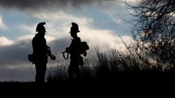 Dua orang mengenakan pakaian tentara tahun 1800-an berbincang saat mengenang kembali pertempuran Austerlitz di dekat desa Moravian selatan Herspice, Republik Ceko (2/11). (Reuters/David W Cerny)