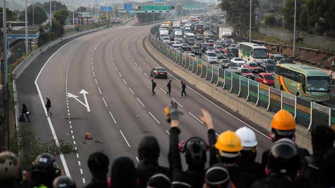 Demonstran prodemokrasi bersorak di jembatan ketika mereka memblokir jalan di luar Chinese University, Hong Kong, Rabu (13/11/2019). Gerakan antipemerintah Hong Kong yang telah berlangsung selama lima bulan bertindak semakin keras. (AP Photo/Kin Cheung)