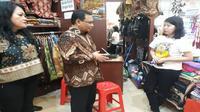 Asisten Deputi Direktur Bidang Pelayanan BPJS Ketenagakerjaan Kanwil Banten, Mulyana, tengah memberikan sosialisasi manfaat penggunaan BPJS Ketenagakerjaan, kepada salah satu penjaga tenant di Tangcity Mall, Tangerang (Foto:Liputan6.com/Pramita T)