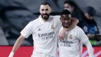 Striker Real Madrid, Karim Benzema bersama Vinicius Junior melakukan selebrasi usai mencetak gol ke gawang Granada pada laga Liga Spanyol di Stadion Alfredo Di Stefano, Kamis (24/12/2020). Real Madrid menang dengan skor 2-0. (AP/Bernat Armangue)