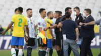 Pemain Brasil dan Argentina berbicara dengan otoritas kesehatan saat pertandingan kualifikasi Piala Dunia 2022 dihentikan di stadion Neo Quimica Arena di Sao Paulo (5/9/2021). Otoritas kesehatan Brasil menyebut empat pemain Argentina telah melanggar aturan karantina. (AP Photo/Andre Penner)