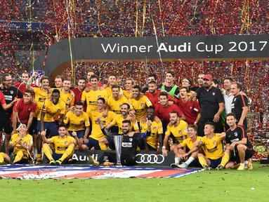 Tim Atletico Madrid merayakan kemenangannya setelah meraih trofi pada final Audy Cup 2017 di Munchen, Jerman (2/8). Atletico menang 5-4 atas Liverpool lewat adu penalti setelah bermain imbang 1-1. (AFP Photo/Christof Stache)