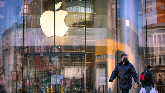 Warga berjalan melewati Apple Store yang tutup di Beijing, China, Selasa (4/2/2020. Belum diketahui bagaimana nasib Apple Store lainnya yang sudah ditutup sejak 1 Februari lalu lantaran wabah virus corona. (AP Photo/Mark Schiefelbein)