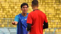 Pelatih Arema, Milan Petrovic, memberikan instruksi kepada Arthur Cunha. (Bola.com/Iwan Setiawan)