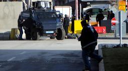 Kendaraan taktis mendekati seorang pria yang tergeletak di tanah, di luar kantor polisi di Gaziantep, Turki, Selasa (10/1). Seorang perwira polisi terluka ringan akibat penyerangan yang dilakukan pria tersebut bersama rekannya yang kabur. (AFP PHOTO/STR)