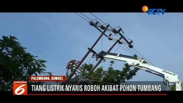Tiang Listrik di Palembang nyaris roboh dan patah lantaran tertimpa pohon tumbang.