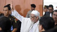 Terpidana kasus terorisme Abu Bakar Baasyir melambaikan tangan kepada para pendukungnya usai menjalani persidangan di Jakarta, (16/06/2011). (AFP Photo/Romeo Gacad)